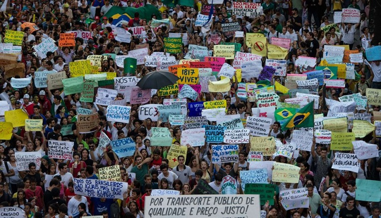 Thousands of people march in the center of Recife, state of Pernambuco, Brazil, on June 20, 2013, during a protest of what is now called the 'Tropical Spring' against corruption and price hikes. Brazilians took to the streets again on a new day of mass nationwide protests, demanding better public services and bemoaning massive spending to stage the World Cup. More than one million people have pledged via social media networks to march in 80 cities across Brazil, as the two-week-old protest movement -- the biggest seen in the South American country in 20 years -- showed no sign of abating.  AFP PHOTO / YASUYOSHI CHIBA